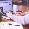 Imagem: mulher digitando no notebook com caneca e caderno de anotações ao lado
