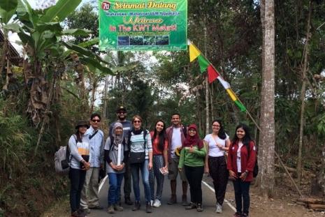 """Equipe """"Landslide"""" sob um cartaz feito pela Vila em homenagem aos estudantes"""