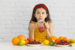 Menina de vestido amarelo tomando suco no canudo com mesa cheia de frutas a sua frente