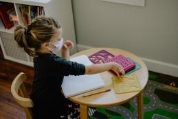 criança com máscara brincando sentada em uma mesa