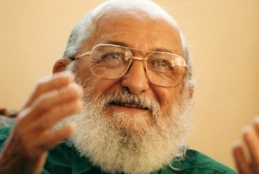 Paulo Freire sorrindo com as mãos levemente suspensas