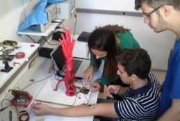 Alunos realizando teste com a prótese robótica