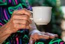Mão direita de uma mulher idosa segurando uma xícara branca. Ao fundo sua outra mão está apoiada sobre a perna, recoberta por um tecido estampado.