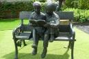 Escultura de duas crianças lendo um livro em uma cadeira, dentro de um jardim