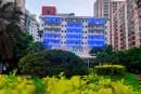 Prédio da reitoria da UFF iluminado com luzes azuis. Diante dele, um jardim com plantas em diferentes tons de verde.