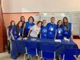 Professora rodeada de alunos vestidos com uniforme azul que identifica o projeto em frente a uma mesa