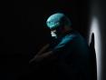 Um profissional da saúde vestido com EPIs sentado no chão, em um lugar escuro
