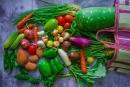 Legumes coloridos em cima de uma superfície saindo de uma sacola de feira