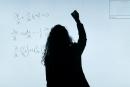 sombra de uma mulher fazendo contas em um quadro