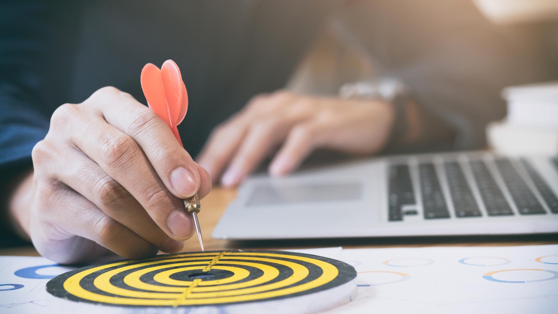 Foto de pessoa colocando um dardo no centro de um alvo