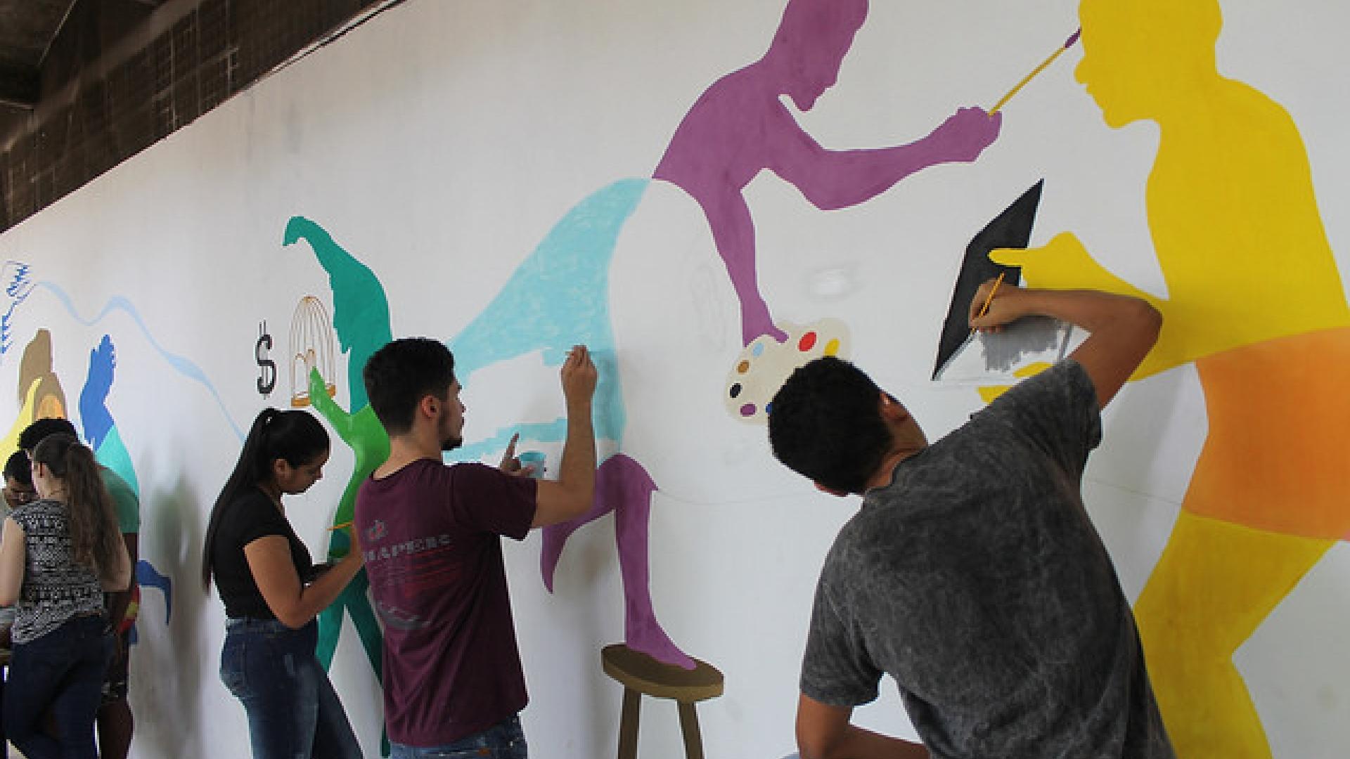 Imagem: alunos pintando silhuetas coloridas em um muro branco