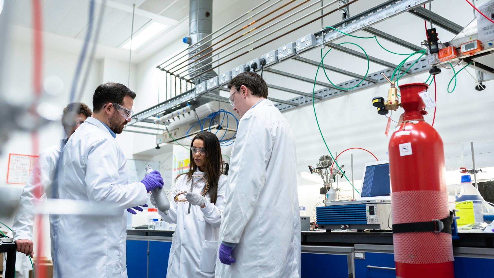 Cientistas de jaleco interagem em um laboratório médico