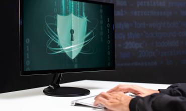 Foto de computador mostrando uma fechadura na tela. Mãos digitando no teclado.
