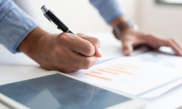 Close up de mão masculina segurando caneta sobre papel com gráficos.