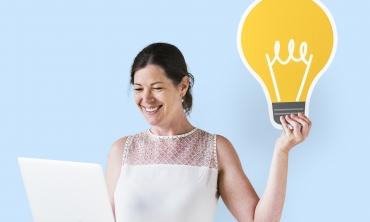 Mulher segurando um tablet em uma das mãos e um objeto no formato de lâmpada em outra mão.