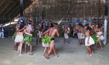 grupo indígena formando um círculo, realizando uma dança de casais com indumentária típica em um ambiente espaçoso com telhado de palha. Em segundo plano há pessoas não-indígenas assistindo a apresentação.