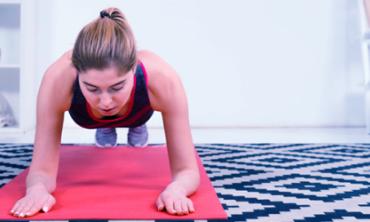 """Mulher realizando exercício de """"prancha"""" sobre tapete de yoga"""