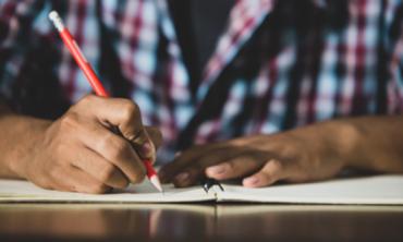 close da mão de um jovem escrevendo em um caderno