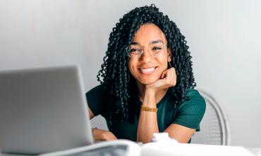 Mulher negra de óculos sorrindo sentada em frente a mesa com laptop