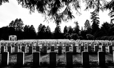 Imagem em P&B de várias lápides em um cemitério