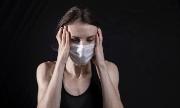mulher com máscara com as mãos sobre o rosto, com expressão tensa