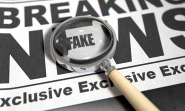 """Imagem de uma lupa e jornal escrito """"Breaking fake news"""""""