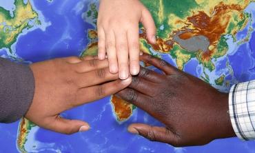 #pratodos verem: Três mãos unidas sobre o mapa mundi