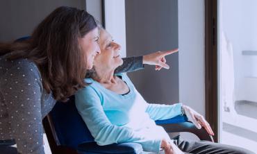 Foto de idosa e mulher olhando através da janela e sorrindo