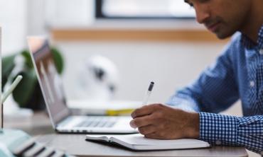 Homem com laptop aberto anotando algo em um caderno