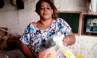 Foto de mulher segurando saco plástico contendo alimentos não perecíveis