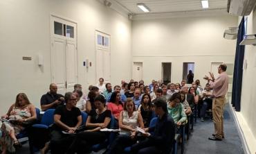 Foto de uma sala de reunião, em que aparece o Prof. Fábio Passos palestrando para um grupo de gestores da UFF.