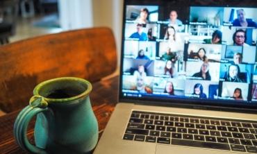 Foto de laptop aberto em cima de uma mesa com a tela mostrando um programa aberto de webconferência. Ao lado do laptop há uma caneca verde.