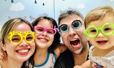Foto do servidor Eduardo ao lado da esposa e das suas duas filhas com óculos coloridos e divertidos